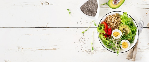 Breakfast bowl with oatmeal, paprika, avocado, lettuce, microgreens and boiled egg. Premium Photo