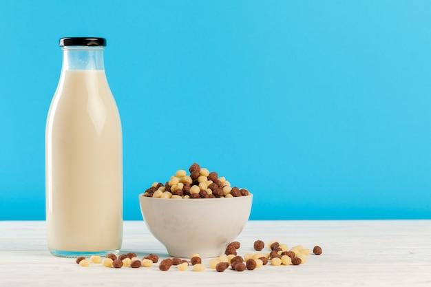 青い背景のガラスの朝食シリアルボールと牛乳 Premium写真