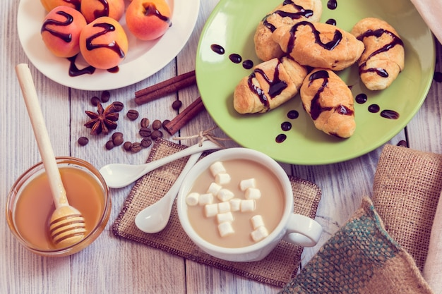 Breakfast of coffee, croissants, apricots, honey, cinnamon and anise Premium Photo