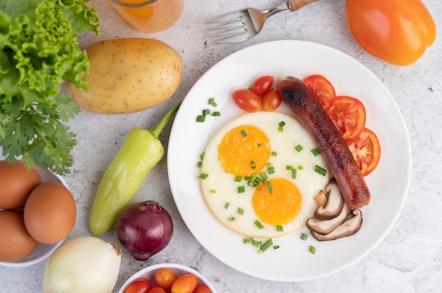 Breakfast consisting of bread, fried eggs, tomatoes, chinese sausage and mushrooms. Free Photo