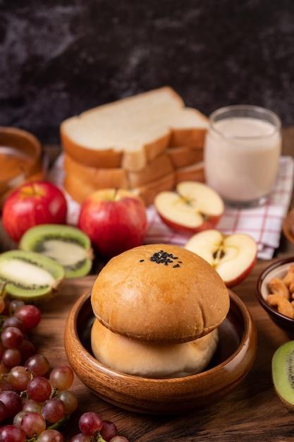 朝食は、木製のテーブルにパン、リンゴ、ブドウ、キウイで構成されています 無料写真