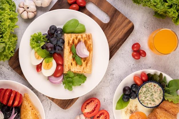 Завтрак состоит из хлеба, вареных яиц, салата из черного винограда, помидоров и нарезанного лука. Бесплатные Фотографии
