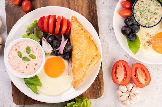 Завтрак состоит из хлеба, жареного яйца, заправки для салата, черного винограда, помидоров и нарезанного лука. Бесплатные Фотографии