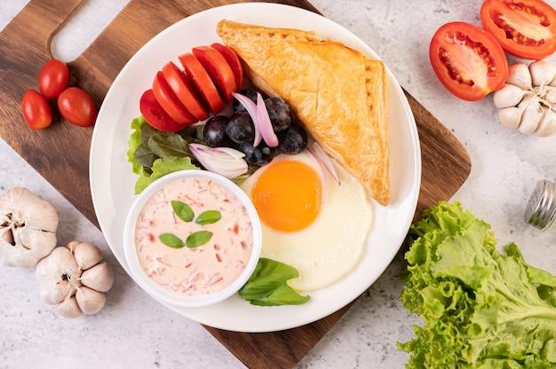 朝食は、パン、目玉焼き、サラダドレッシング、黒ブドウ、トマト、スライスした玉ねぎで構成されています。 無料写真