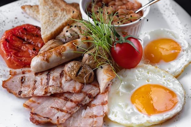朝ごはん。卵、ベーコン、キノコ、トースト、豆、白い皿の上 Premium写真