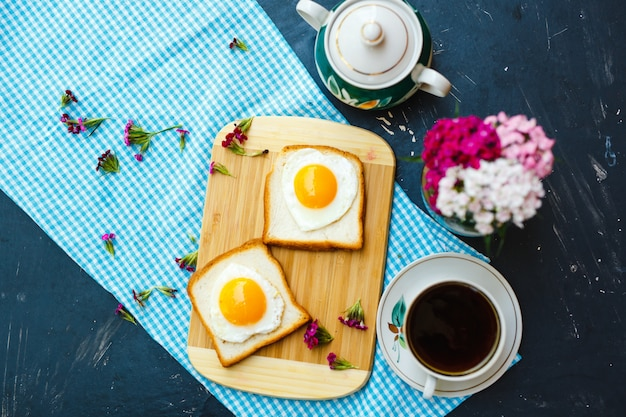 Breakfast freshly prepared with heart shaped fried eggs and tea cup Premium Photo
