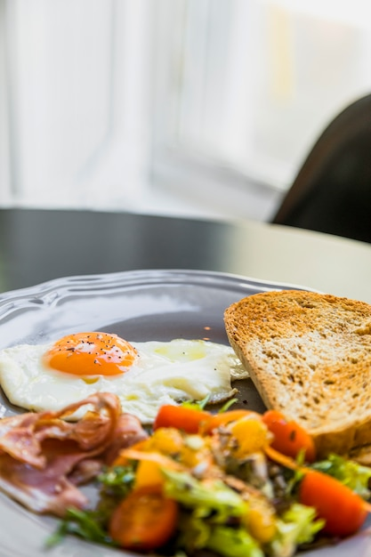 Breakfast gray plate with egg; bacon; toast and salad on table Free Photo