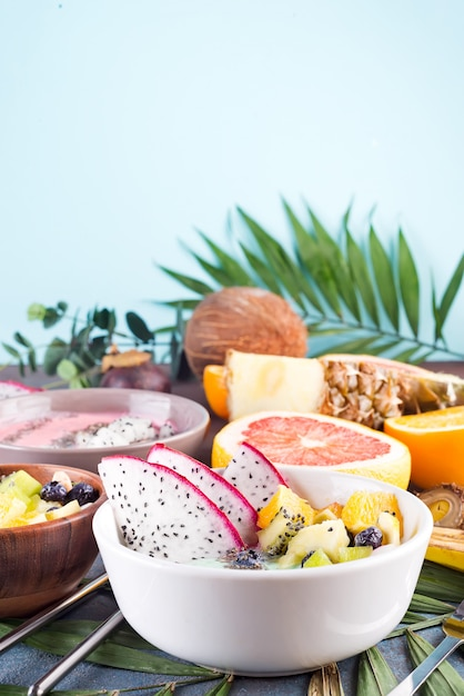 Breakfast green yoghurt bowl topped with pitaya, pineapple, chia seeds and berries with palm leaf on stone background, top view Premium Photo
