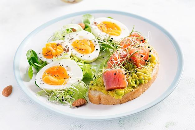 Prima colazione. un sano panino aperto su pane tostato con avocado e salmone, uova sode, erbe aromatiche, semi di chia sulla zolla bianca con lo spazio della copia. cibo proteico sano. Foto Gratuite