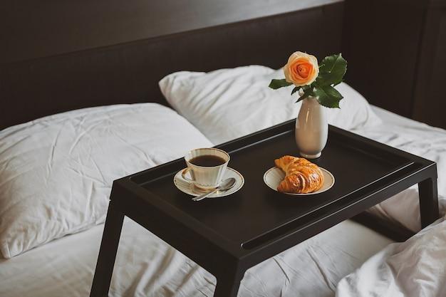 Завтрак в постели на подносе с розой в вазе Premium Фотографии