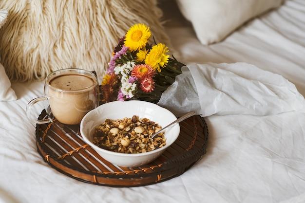 花束とベッドでの朝食します。 Premium写真