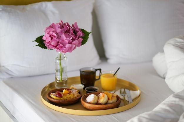ホテルでの朝食。花とベッドで朝食。ベッドでコーヒー、ジュース、チーズケーキ。ベッドで食べる。怠けた週末。 Premium写真