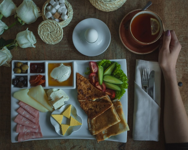 Breakfast menu plate with big selection of foods and cup of tea Free Photo