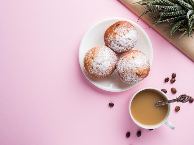 Breakfast muffins coffee milk jug on a pink background. top view flat lay. Premium Photo