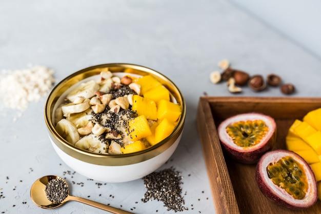 Breakfast oatmeal porridge with fresh fruits, chia seeds and hazelnuts. Premium Photo