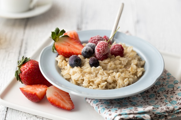 Breakfast oatmeal porridge with fruits berries and coffee cup. Premium Photo