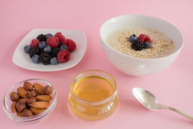 Завтрак: овсянка с ягодами, медом и орехами на розовом фоне. Premium Фотографии