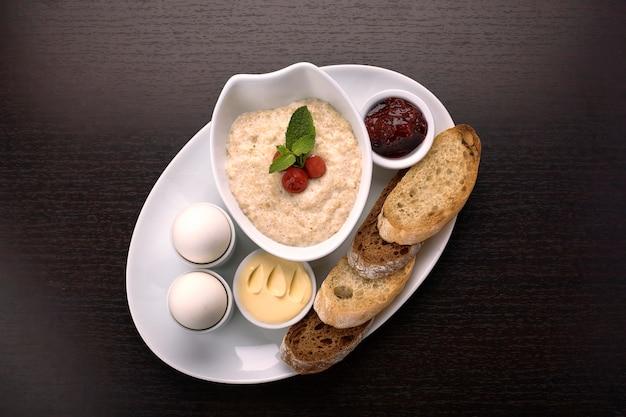 Завтрак из каши, сливочного масла, вареных яиц, джема и тостов, гренок на темной поверхности Premium Фотографии