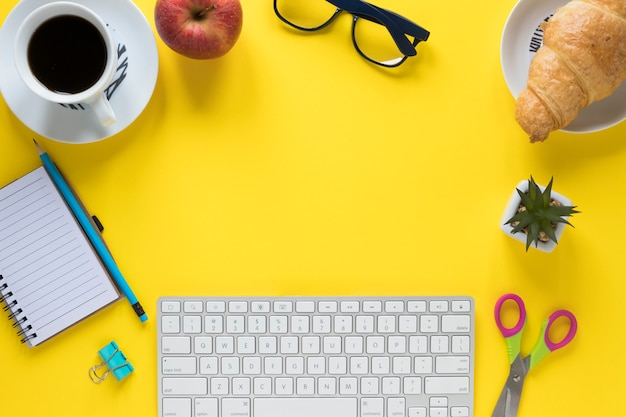 Breakfast; office stationeries and keyboard on yellow background for writing the text Free Photo