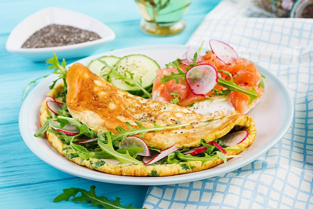Breakfast. omelette with radish, green arugula and sandwich with salmon on white plate Premium Photo