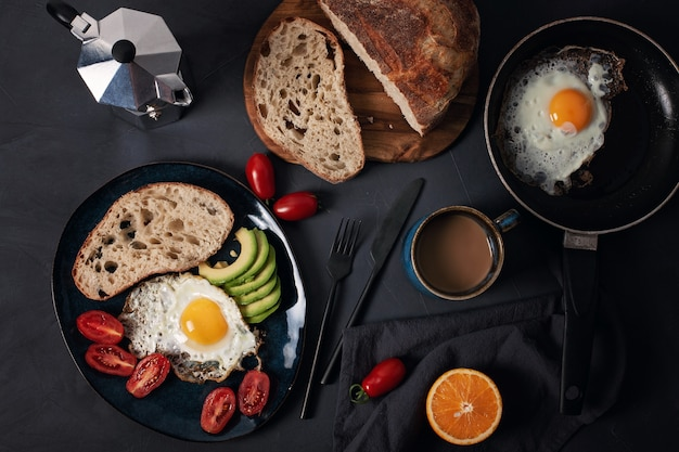Breakfast served with coffee, bread, fried eggs, avocado and tomatoes Premium Photo