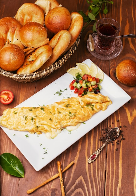 Breakfast snack crepes, omlettes with vegetable salad and bread buns in white plate Free Photo