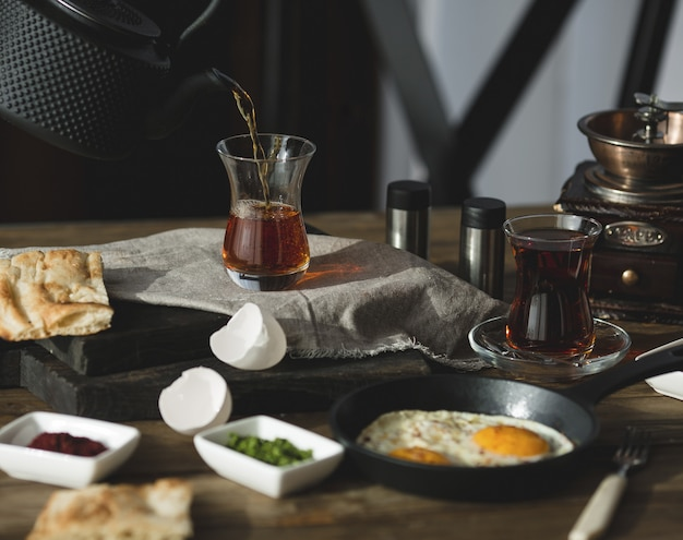 Breakfast table set for two persons with tea glasses and fried eggs Free Photo