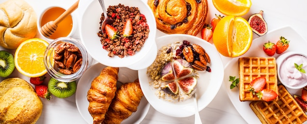 Breakfast table with oatmeal, waffles, croissants and fruits. Premium Photo