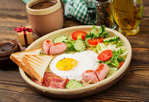 Breakfast on valentine's day - fried egg in the shape of a heart, toasts, sausage, bacon Premium Photo