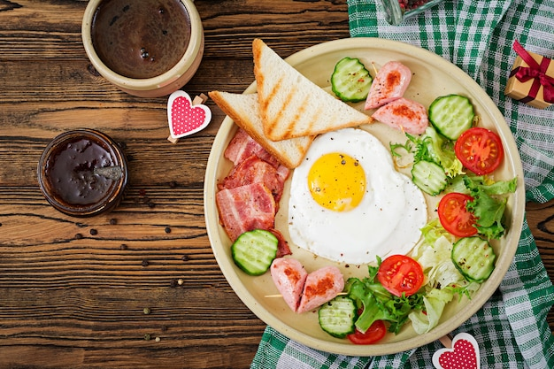 Breakfast on valentine's day - fried egg in the shape of a heart, toasts, sausage, baconnd fresh vegetables. english breakfast. cup of coffee. top view Free Photo
