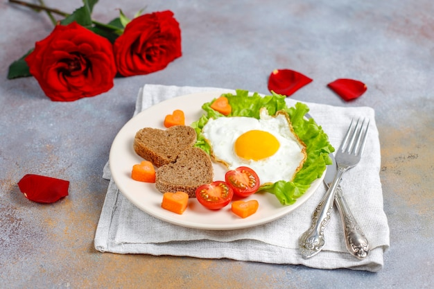 Breakfast on valentine's day - fried eggs and bread in the shape of a heart and fresh vegetables. Free Photo