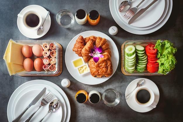 Breakfast with ham, egg, cucumber, milk, orange juice, french bread or baguette on black background Premium Photo