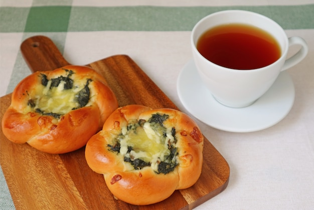 Breakfast with hot tea and spinach and cheese buns Premium Photo