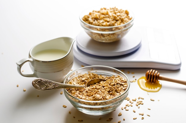 Breakfast with oatmeal porridge on digital kitchen scales, milk and honey on white Premium Photo