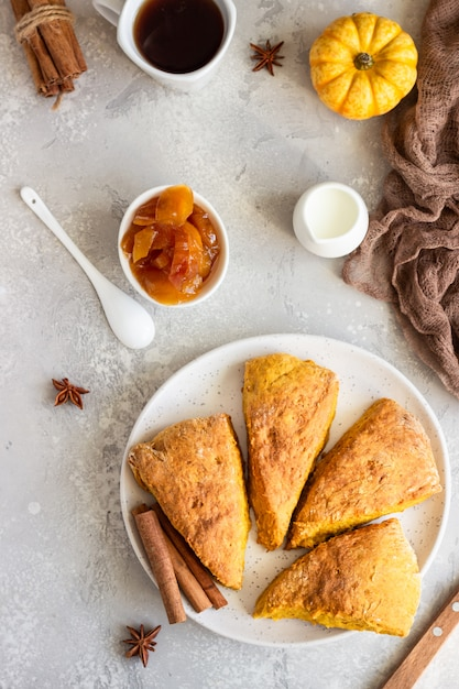 Breakfast with spicy pumpkin scones, a cup of tea and milk. Premium Photo