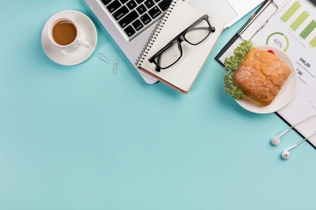 Breakfast with spiral notepad,laptop,eyeglasses,earphones on blue desk Free Photo