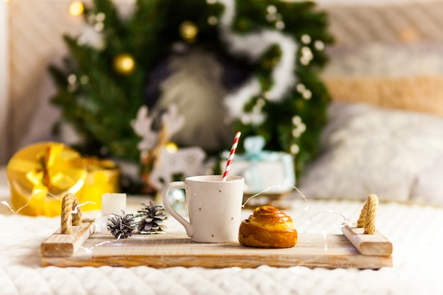 Breakfast on a wooden tray on bed with christmas decoration Premium Photo