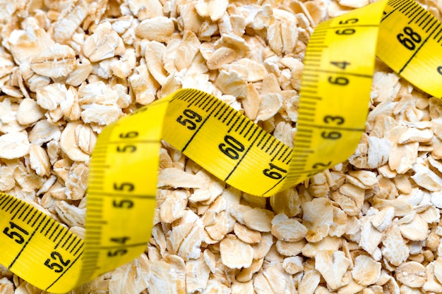 測定テープとオートミールをクローズアップ。健康的な食物繊維の朝食、breakfast身食品 Premium写真