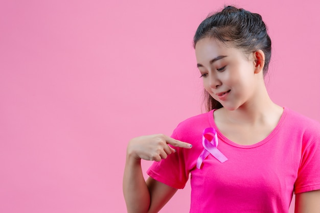 Breast cancer awareness , woman in pink t-shirt with satin pink ribbon on her chest, supporting symbolbreast cancer awareness Free Photo
