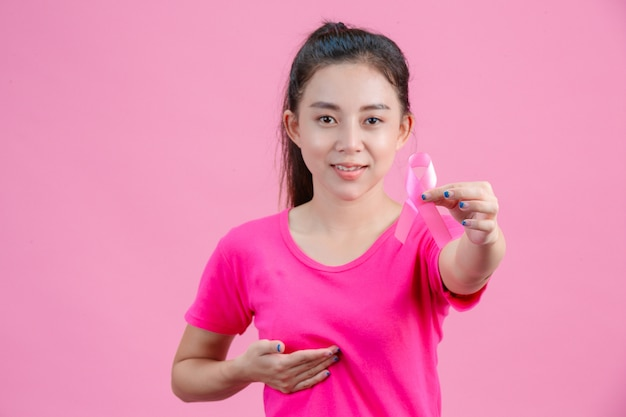 Breast cancer awareness , a woman wearing a pink shirt holding a pink ribbon with the left hand show the symbolthe day against breast cancer Free Photo