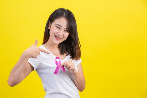 Breast cancer , a woman in a white t-shirt with a satin pink ribbon on her chest, a symbol for breast cancer awareness Free Photo
