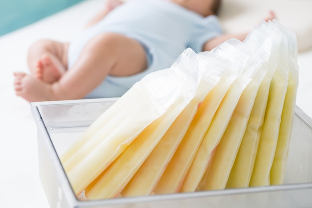 Breast milk frozen in storage bag and baby lying on background Premium Photo