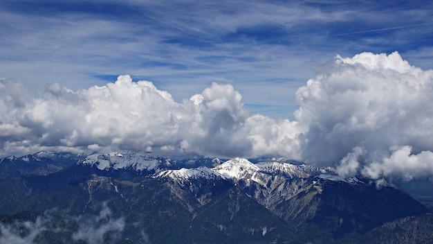 Tiro mozzafiato ad alto angolo di montagne innevate sotto le nuvole e il cielo sullo sfondo Foto Gratuite