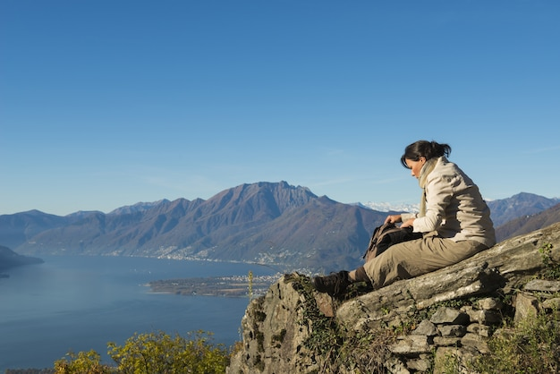 Breathtaking scene of a female sitting on the top of the mountain Free Photo