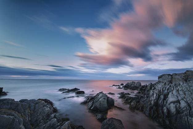 Scenario mozzafiato di nuvole colorate che si riflettono nello specchio del mare alle lofoten, norvegia Foto Gratuite