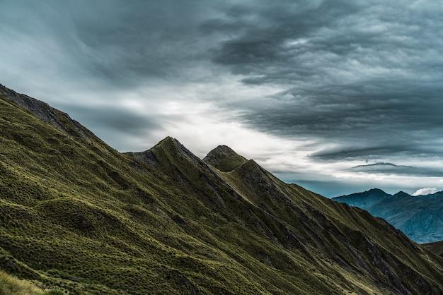 Scenari mozzafiato dello storico roys peak che sfiorano il cielo cupo della nuova zelanda Foto Gratuite