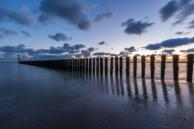 オランダ、ゼーラント州のウエストカペレの海の桟橋に沈む夕日の息をのむような風景 無料写真
