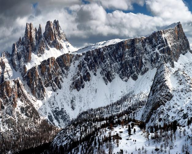 冬のイタリアアルプスのドロミテンで曇り空の下で雪に覆われた岩の息をのむような風景 無料写真