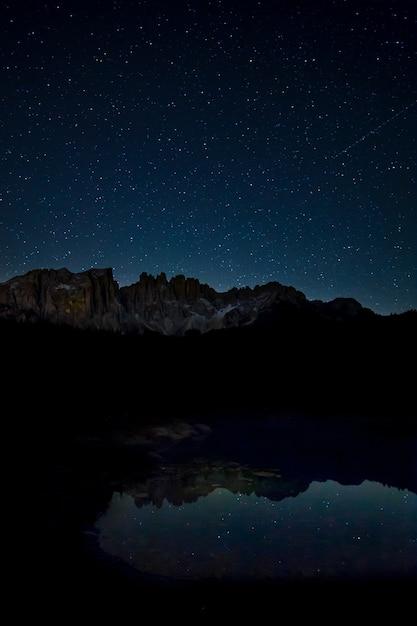 밤에 호수에 비친 별이 빛나는 하늘과 바위 절벽의 숨막히는 풍경 무료 사진