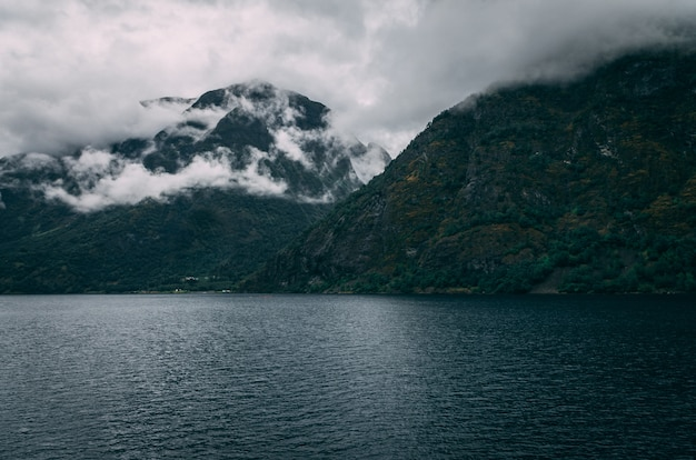 Breathtaking shot of a lake surrounded by the snowy mountains under the foggy sky in norway Free Photo